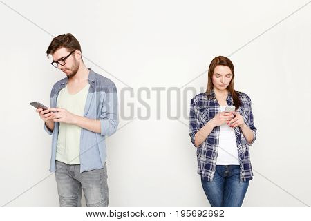 Young married couple browsing to social media using smartphones standing at white studio background, isolated. Gadget addiction concept