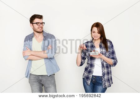 Couple in casual at white isolated background. Woman eating healthy food from take away box and man looking at it with disgust