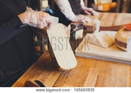 Shop assistant cutting hard cheese, pecorino cheese in grocery shop, closeup