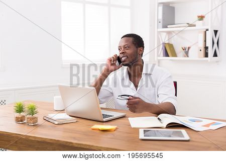 Satisfying call. Young black businessman has mobile phone talk in modern white office interior.