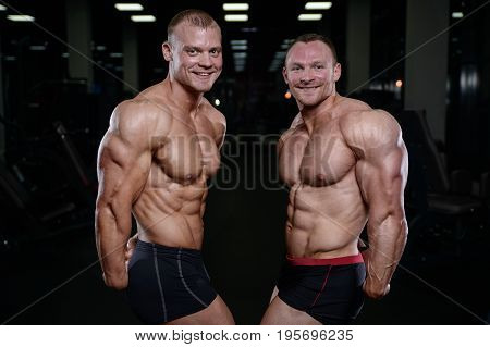Two Brutal Strong Athletic Men Pumping Up Muscles And Train In Gym Workout