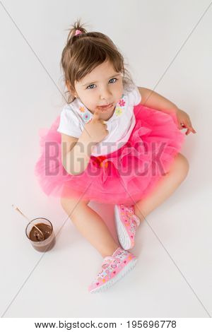 Image of little hungry children girl sitting over white background. Looking at camera eating chocolate dessert.