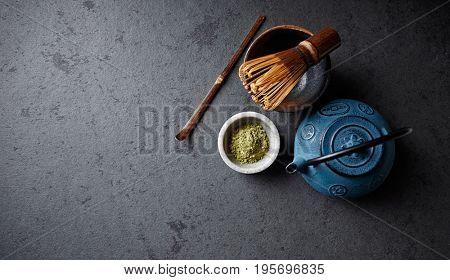 An arrangement of a cast iron tea pot, matcha powder and tea whisk