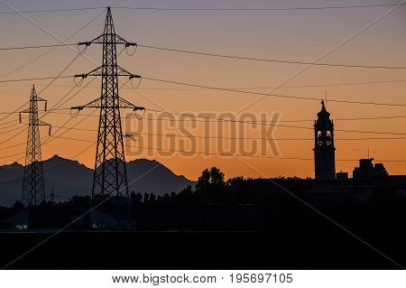 Silhouette of high voltage power line cables in an orange evening sunset