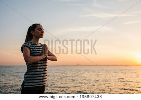 Young beautiful girl practicing yoga and meditation on the rocks next to the sea at sunset. Yoga. Meditation. Recreation. Vacation. Relaxation.