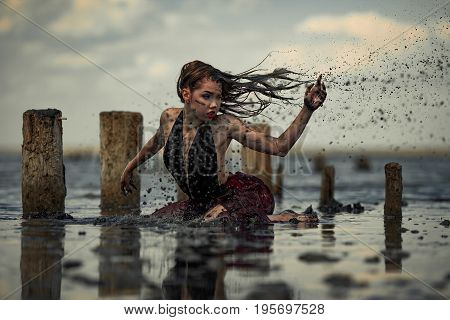 Young woman bathing in therapeutic water of mud estuary, next there are wooden columns and mud splashes. Spa.