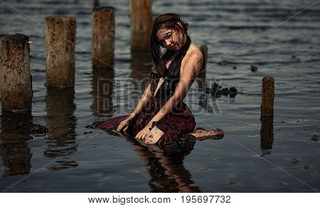 Young woman bathing in therapeutic water of mud estuary, next there are her reflection and wooden columns. Spa.