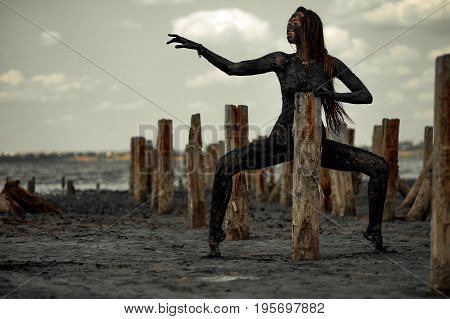 Young woman smeared with therapeutic mud and stands near wooden column. In distance there is mud estuary. Spa.