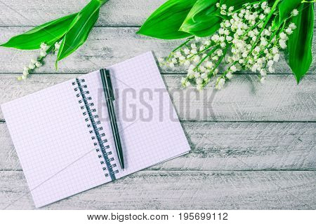 blank notebook, pen and lily of the valleys on wooden background. top view copy space.