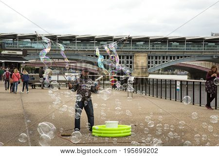 LONDON, UK - JUNE 5, 2017: Man doing giant soap bubbles as a living on the queen's walk in London, UK