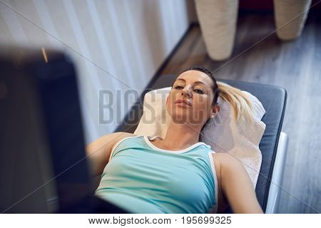 Attractive fit middle-aged woman doing vacuum therapy for prevention and strengthening of tissue