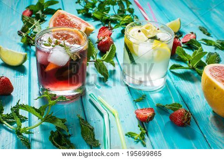 Glass of alcohol cold coctail decorated with ice, fruit and mint staying on wood table. Fresh juice on background with lemon, strawberry, lime.