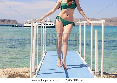 young Caucasian girl in a green swimsuit on the blue pier, by background blue Ionian sea, Balos, Greece.