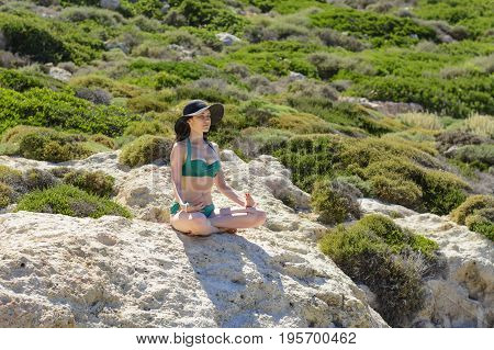 Woman meditating in Lotus pose on the cliffs of the beautiful beach of Balos, Greece. the concept of rest, relaxation, spiritual peace, qigong
