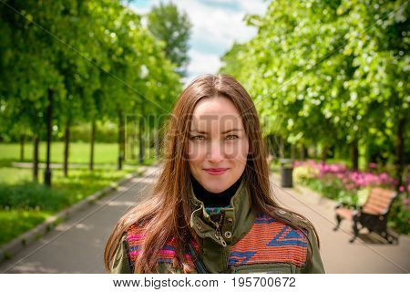 Beautiful young girl with long hair and in colored jacket in the summer park. The effect of perspective.