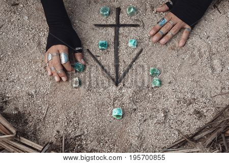close up of woman hands with magical symbols on the ground
