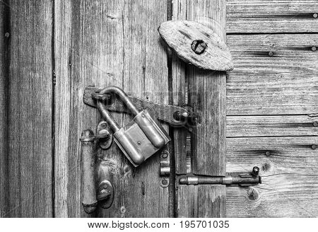 Wooden door surface with handle old padlock old metal and wooden latches.Black and white texture.