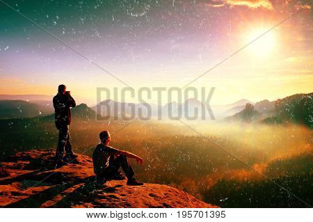 Film grain effect. Hiker and photo enthusiast stay with tripod on cliff and thinking. Dreamy fogy landscape blue misty sunrise in a beautiful valley below