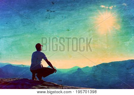 Film Grain. Runner In Red Cap And  In Dark Sportswear In Squatting Position On A Rock In Heather Bus