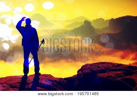 Film Grain. Silhouette Of Tourist With Poles In Hand. Hiker Stand On Rocky View Point Above Misty Va