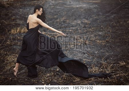 Sad girl standing on the burned-out land. Concept of environmental disaster. Global problems with ecology. Young attractive multi-racial Asian Caucasian woman in black dress on nature