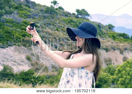 Woman traveler makes a self in the background beautiful natural view mountain on the island of Crete. Concept - tourism travel photos from vacation