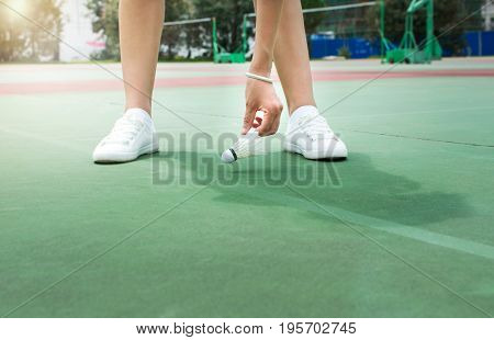 Girl Collecting Badminton Ball On Field