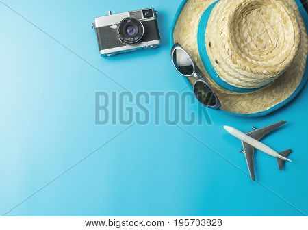Summer travel accessories on bright blue copy space