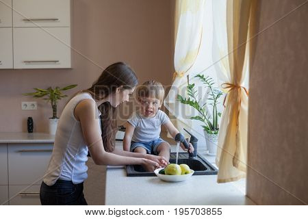 mother and young son wash their vegetables in the kitchen sink