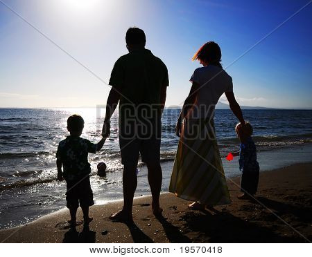 Young family having fun playing at the beach in the morning - silhouette