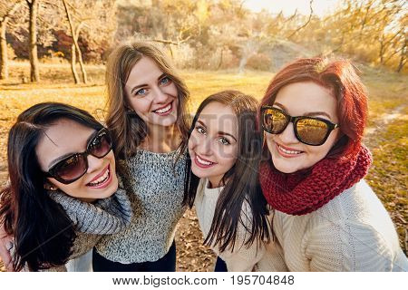 Portrait of happy smiling young friends in autumn park
