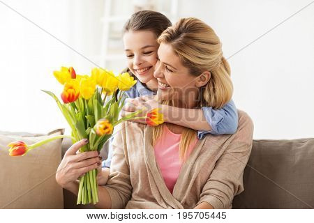 people, family and holidays concept - happy girl giving tulip flowers and hugging her mother at home