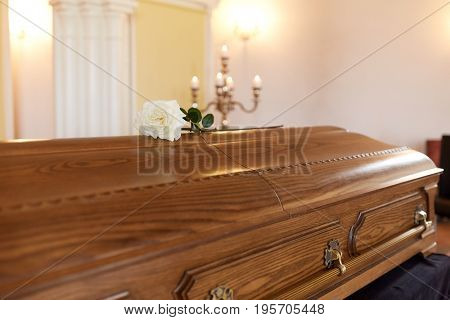 funeral and mourning concept - white rose flower on wooden coffin at funeral in church