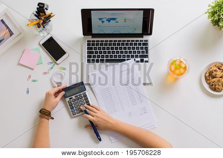 business, accounting and freelance concept - woman hands with calculator, papers and laptop computer working at office