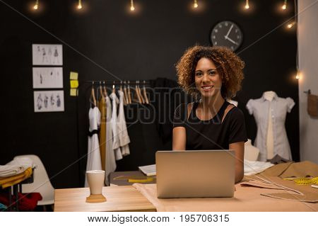 A young fashion designer on her atelier working with a laptop