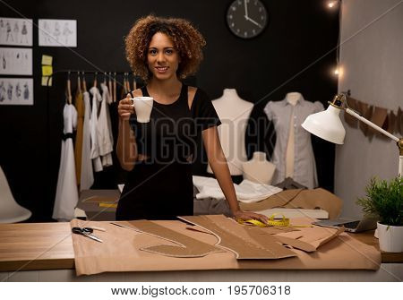 Young fashion designer on her atelier making a pause and drinking coffee