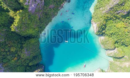 Aerial drone view of tropical turquoise water Loh Samah Bay surrounded by limestone cliffs, Phi Phi islands, Thailand