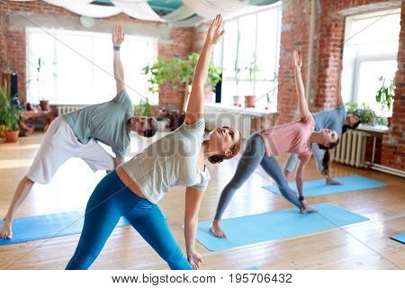 fitness, sport and healthy lifestyle concept - group of people doing yoga in triangle pose at studio