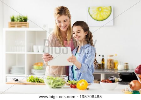 healthy eating, family and people concept - happy mother and daughter cooking vegetables for dinner using online recipe on tablet pc computer at home kitchen