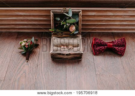 Golden rings in the beautiful rustic box and stylish men wedding accessories on the wooden background. Preparation for wedding concept. Horizontal