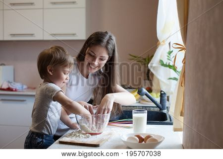 mother and son prepare pie sprinkled with flour