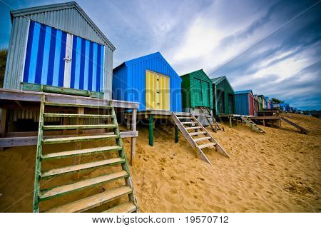Colourful beach huts with dramatic sky
