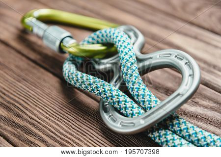 Climbing belay device with rope and carbine on wooden background.