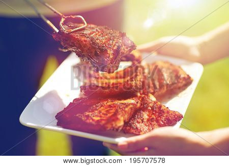 food, people, eating and cooking concept - man with tongs putting barbecue meat on plate at summer party