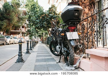 The motorcycle is parked on the street and closed to a special lock against theft.