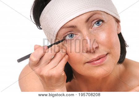 Close up portrait of focused woman looking at camera while putting eyeliner. Isolated on white. Old skin care concept