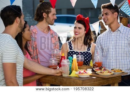 Friends talking while standing by food and drinks at table
