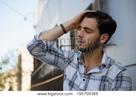 Tensed man with eyes closed sitting by wall