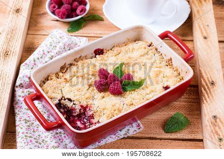 Crumble with raspberries on a wooden background