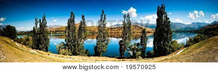 Panoramic landscape view of mountain lake and clear blue sky.